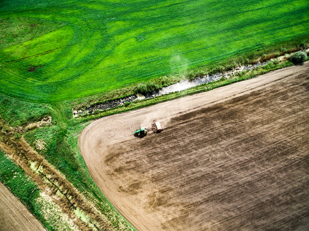 harvester plowing field in spring, view from height Stock Photo