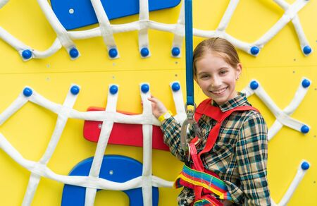 entertainment center: joyful little girl near climbing wall with nets in entertainment center