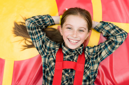 hands on head: smiling joyful girl lying on colorful trampoline in entertainment center