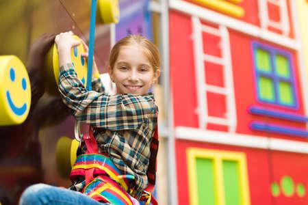 entertainment center: smiling little girl on climbing wall in entertainment center Stock Photo