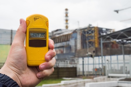 nuclear reactor: radiometer in hand with fourth Chernobyl reactor on the background
