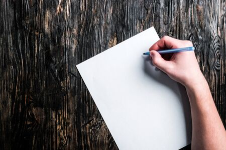 hand with pen and white blank sheet on dark wooden table