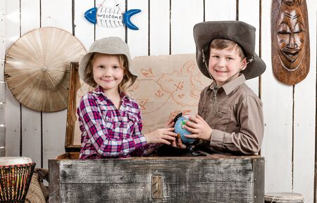 map case: little boy and girl study globe sitting in big old chest