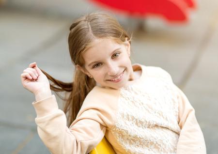 Schattig lachend meisje zittend op stoel met haar in haar hand kijken naar camera Stockfoto - 76648694