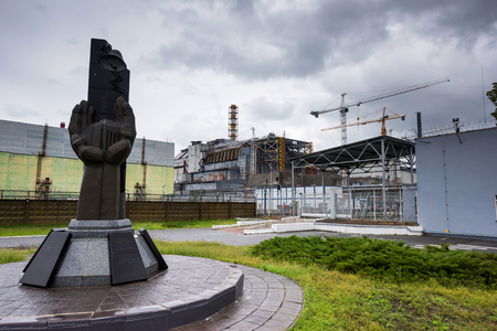 monument to the Chernobyl catastrophe liquidators with fourth reactor on the background Stock Photo