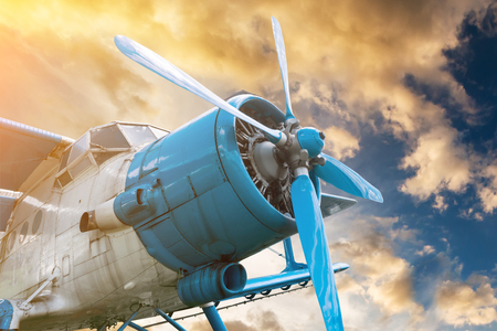 plane with propeller on beautiful bright sunset sky background Reklamní fotografie - 76477212