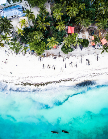 beautiful turquoise ocean meets african island with houses and palms, aerial photo, top view Foto de archivo