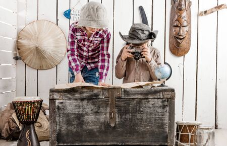map case: two little children in hats watching map on big old chest Stock Photo