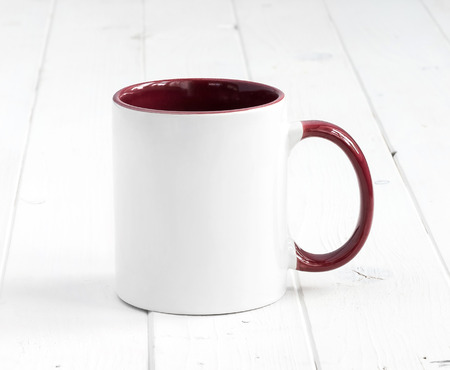 simple white cup with dark red inside and handle on a planked table