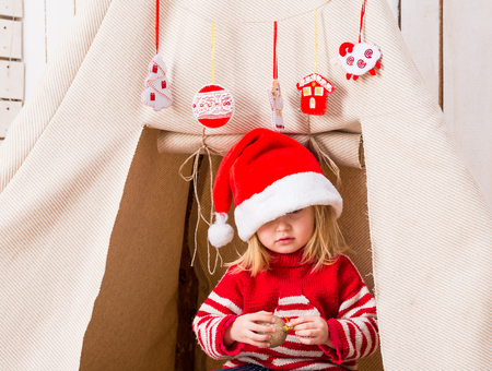 cute little girl in red santa hat over her eyes with toy-ball in hands near wigwam