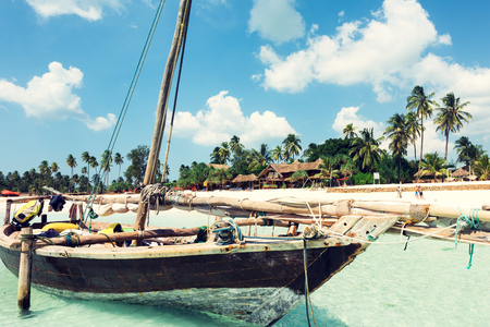 wooden boat on the seashore with beautiful African island and sky on the background