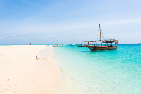 anchored boat on african seashore with blue sky on the background