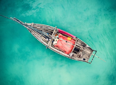 ocean fishing: lonely fishing boat in clean turquoise ocean, aerial photo, top view