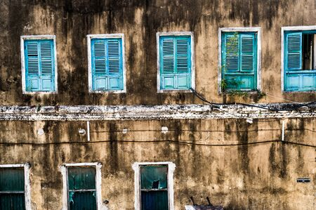dirty neglected house with row of colorful windows in poor african region Stock Photo