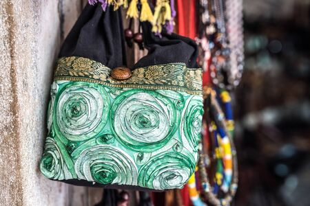 handmade fabric bag hung on a wall for sale in african market street