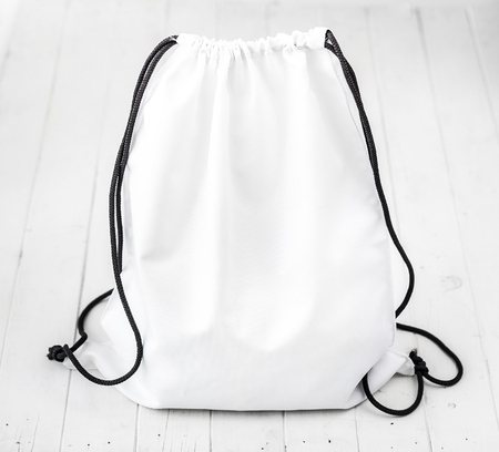 white backpack with black string on planked surface Stock Photo