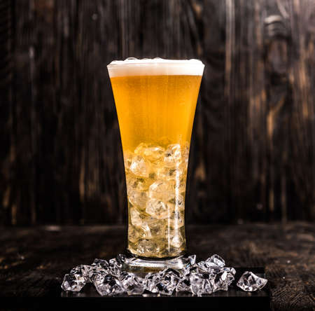 glass of light beer with ice and head of foam on dark wooden background Stock Photo
