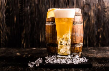 little barrel and glass of light golden beer with ice and lemon, closeup Stock Photo