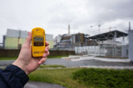 Pripyat, Ukraine - May 29, 2016: radiometer in hand with fourth Chernobyl reactor on the background