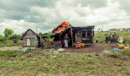 trash the dress: Zanzibar, Tanzania - July, 14, 2016: Editorial use - poor african hut in Zanzibar field with smiling woman and trash around Editorial