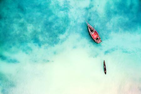 boot en schip in mooie turkooise oceaan dichtbij een eiland, hoogste mening, luchtfoto Stockfoto
