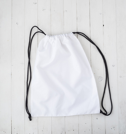 sac: white backpack with black string on planked surface Stock Photo