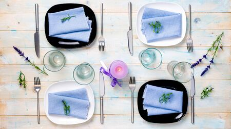 carefully: beautiful table serving for four with purple candle and flowers on wooden background, top view
