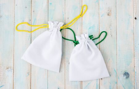 sac: two little gift fabric bags with colorful ties on white wooden surface