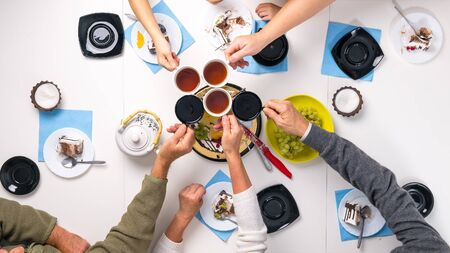 people clanging cups with tea together at the table with delicious desserts, top view Stock Photo