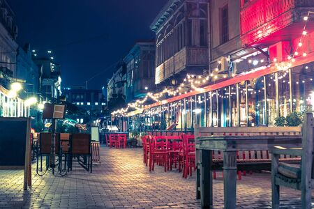 beautiful view of illuminated street cafe in Tbilisi at night