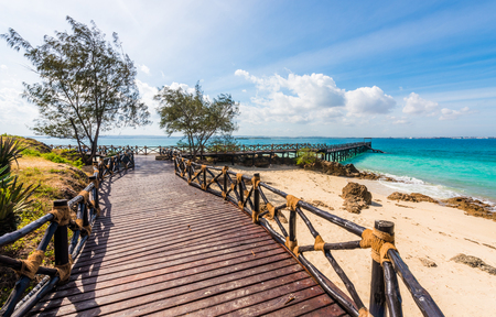 beautiful exotic landscape with wooden pier leading to the blue ocean in Africa Stock Photo