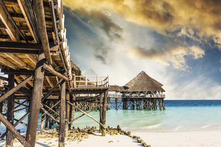 beautiful view of wooden pier with thatched roof in ocean and blue sky Stock Photo