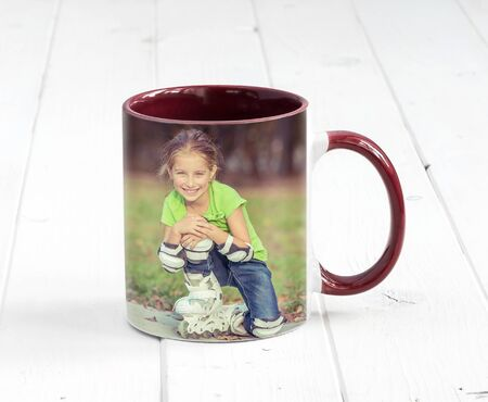 Small bordeaux cup with dark red handle and a print of a little girl
