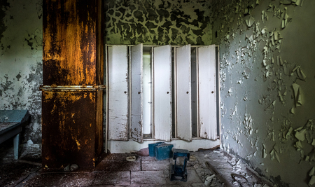 room with peeling paint on walls and lockers in Pripyat school, Chernobyl, Ukraine