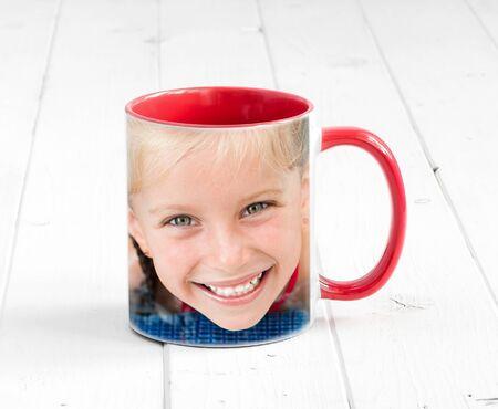 Semplice tazza rossa all'interno con una stampa, sorridente ragazza bionda Archivio Fotografico