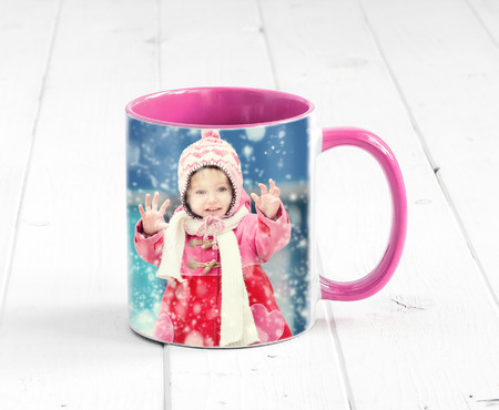 Pink cup with bright pink handle sitting on the table, with a print of girl