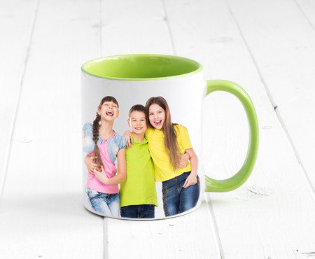 Big cup with bright green inside and a handle sitting on the white wooden table