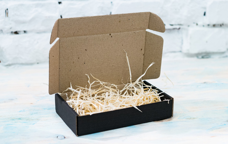 Black gift cardboard box with wooden shavings Stock Photo