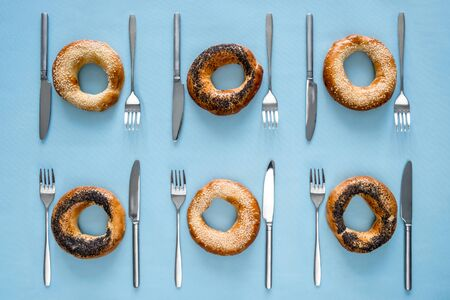 Small dry bagels with poppy seeds and sesame with cutlery on blue background top view Stock Photo