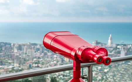 Coin operated red binocular towerviewer on observational deck with view on the sea and city