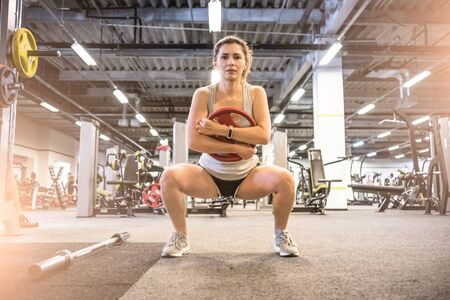 girl doing squats in a gym Stock Photo