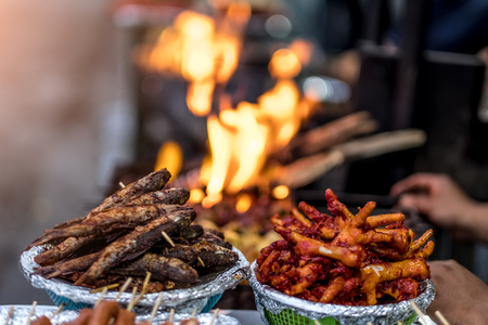 Freshly fried fish and deep fried chicken feet near the fire on the Nepalese street market