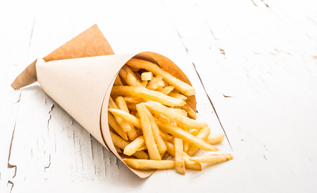 Fresh french fries chips wrapped in brown craft paper on white wooden surface with cracking paint