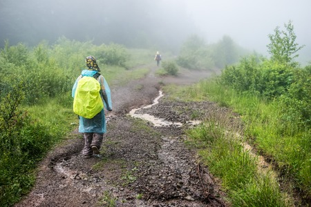 Hiker tourist in raincoat travels to green mountain forest in the fog with the yellow backpack in rainy weather.