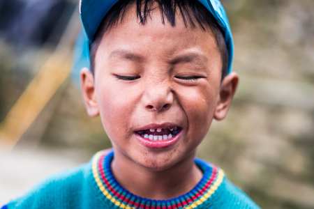 Annapurna track, Nepal - 08 October 2017: Portrait of Nepalese boy with dirty face living near Annapurna track, Himalayas.