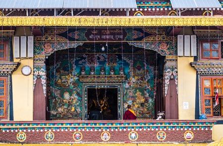 Kathmandu, Nepal - 06 October 2017: Well-designed entrance to the Boudhanath Stupa, Kathmandu, Nepal. Monk prays near the entrance alone.