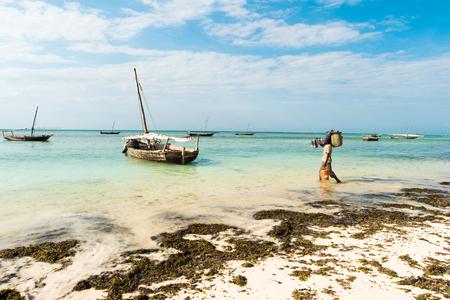 Zanzibar, Tanzania - July 09, 2016: Local fisherman going to boat for daily fishing trip, shoreline with weed on it, Zanzibar