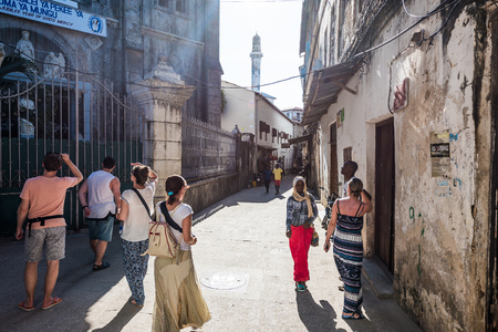 Zanzibar, Tanzania - July 14, 2016: Tourists watching architecture of Zanzibar, Tanzania and meeting local folks, facing poverty