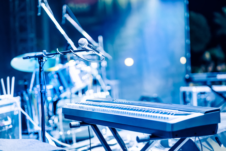 Microphone and synthesizer on concert stage with defused bokeh lights blue colour background Stock Photo