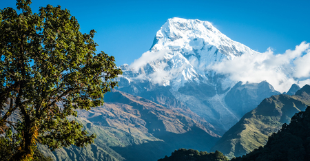 Snow covered beautiful mountain peak against the blue sky in Annapurna, Nepal